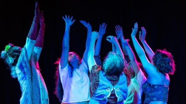 A group of people on stage reach up with their arms, in blue lights.