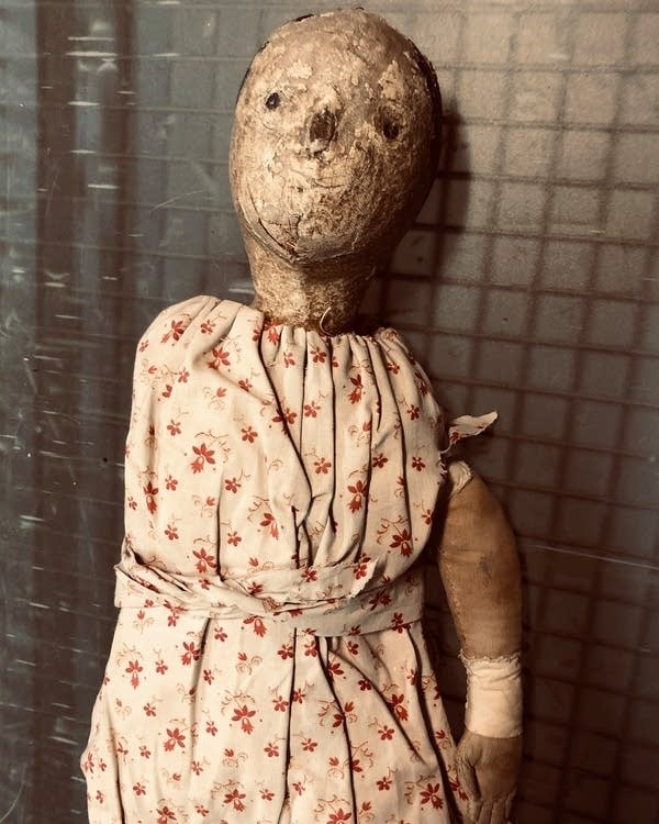 A doll with a cloth head and white dress with small red flowers.