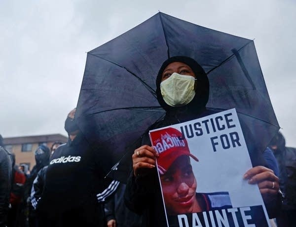 A person holds a sign while standing under an umbrella.