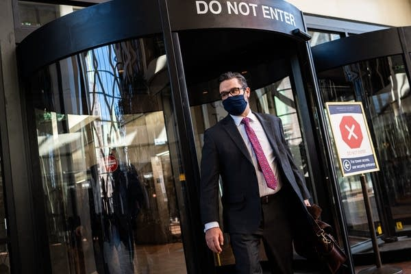 A man with a black mask walks out of revolving doors.