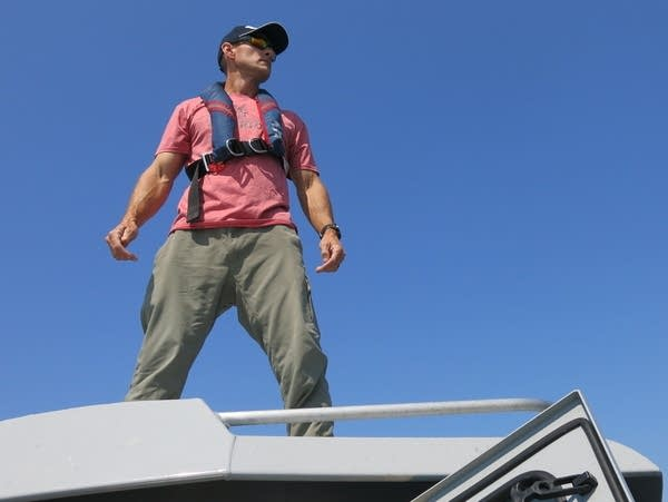 A man stands on top of a boat.