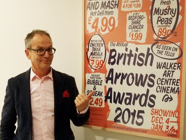 Charlie Crompton stands by a poster for a past British Arrows show.