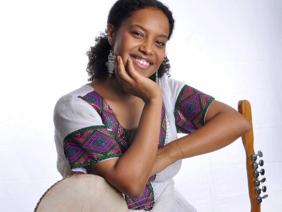 A woman posing with a krar