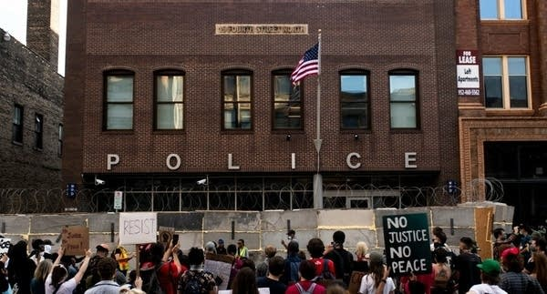 Demonstrators protest outside a police station.
