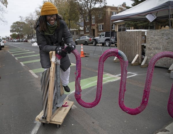 A woman rides on a wooden board with wheels connected to a bike rack