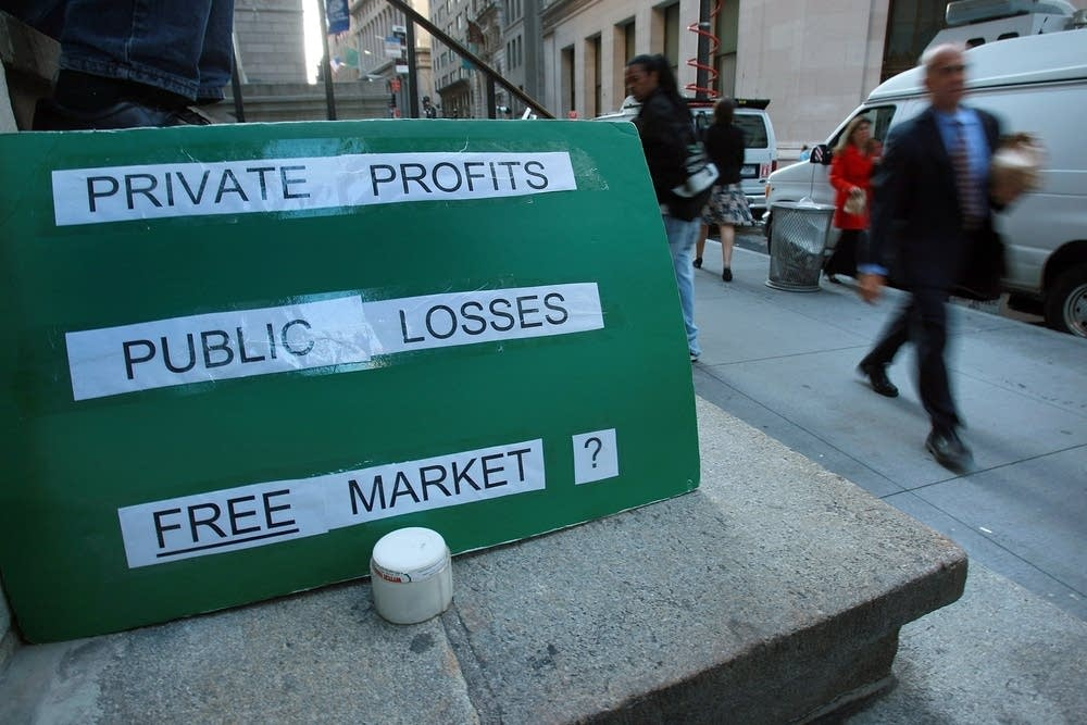 A sign questions the market system on Wall St.