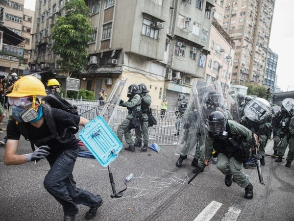 A protester flees from baton-wielding police in Hong Kong