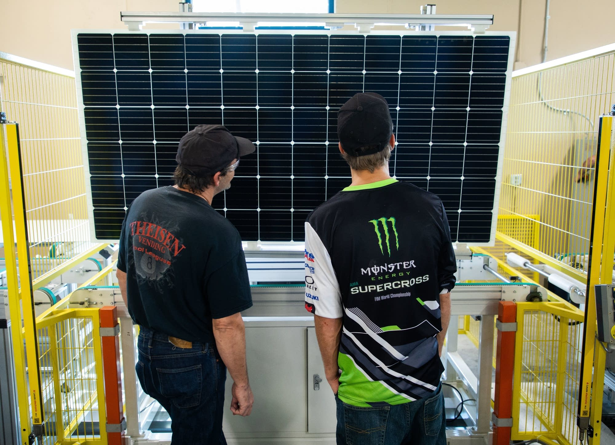 Jared Brincefield and Allen Mart inspect a nearly completed solar panel