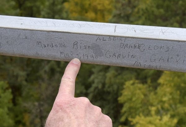 A finger points at names etched on a metal bar above treetops.