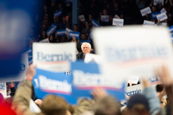 A man speaks behind a crowd of blue and white signs.