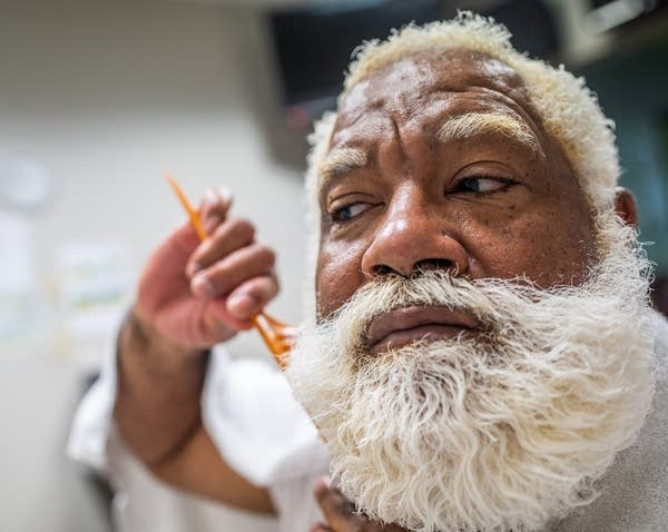 Santa Larry Jefferson combs his beard as he prepares for photo shoots.