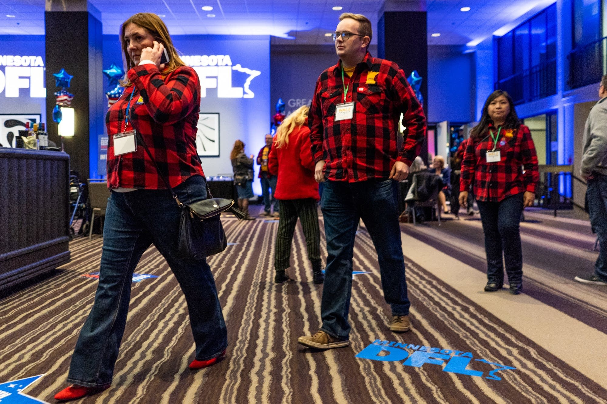 Supporters and staff of Tim Walz wear matching custom red flannel shirts.