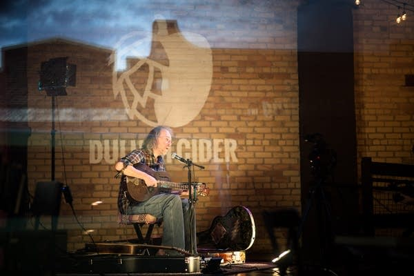Charlie Parr photographed through the glass at a virtual performance.
