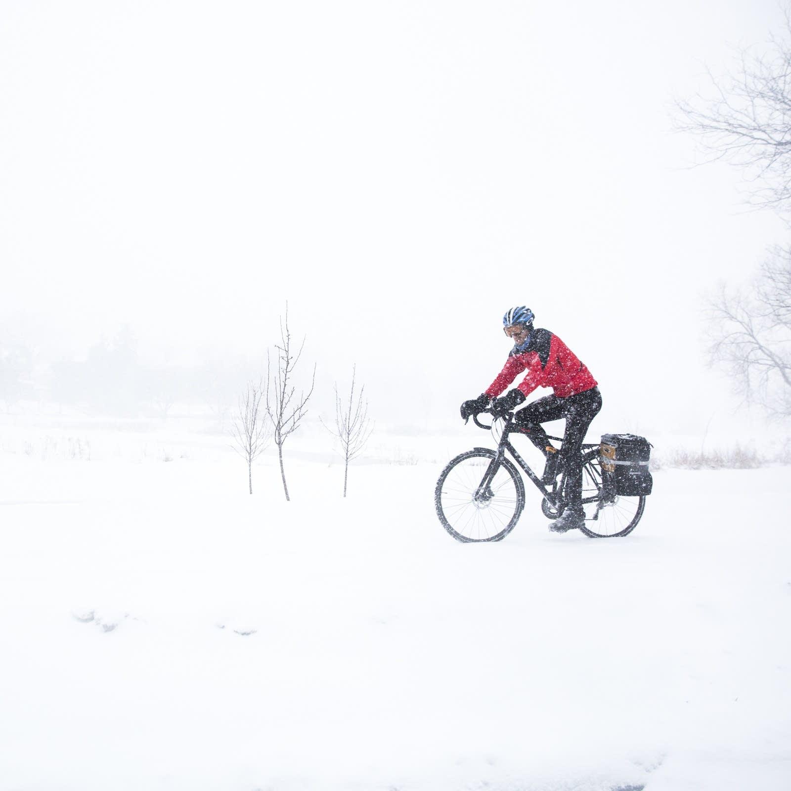 A person bikes through heavy snow around Lake of the Isles