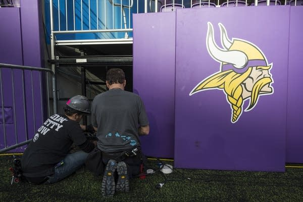 Two construction workers prepare US Bank Stadium