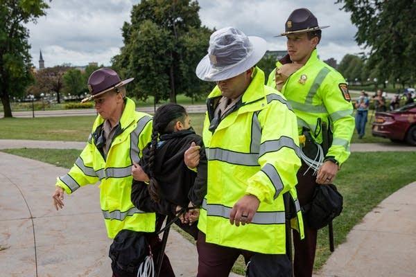Three police carry one man.