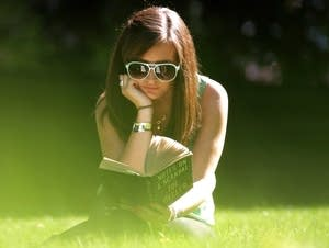 A woman reads in Victoria Tower Gardens