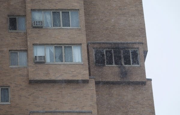 Black fire damage can be seen from a window of the high rise apartment.