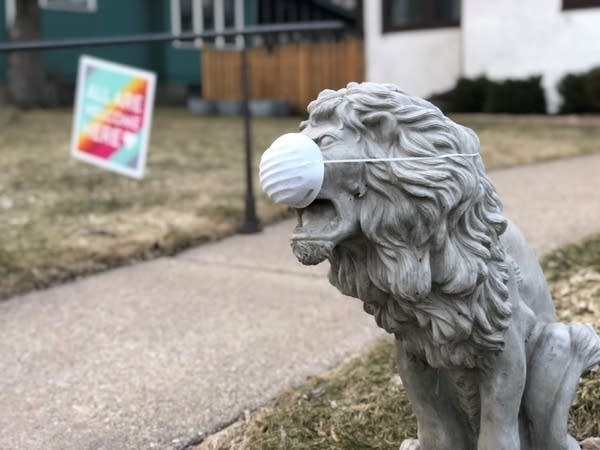 A concrete lion wears a mask in front of a house.