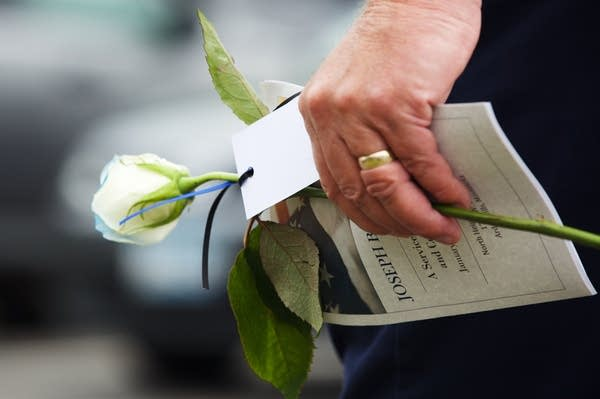 A mourner carries a white rose and a program from the funeral.