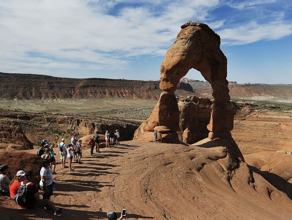 Tourists line up for photos at Delicate Arch in Arches National Park near Moab, Utah, in June 2016. Arches and several other national parks have closed down amid the coronavirus pandemic.