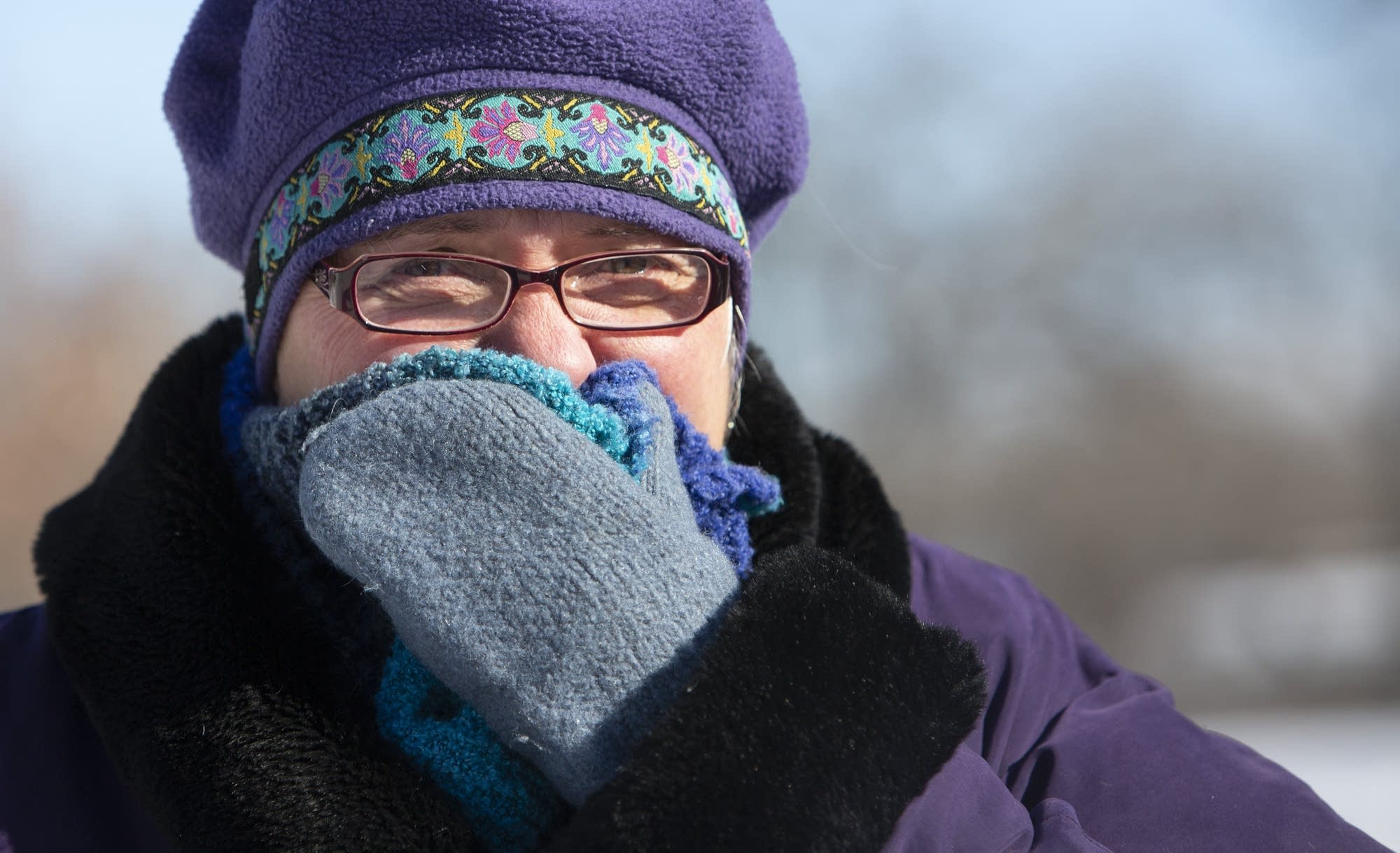 Mary Preus covers her face as she looks at a frozen Minnehaha Falls.