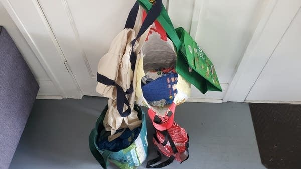 Photo of various tote bags hanging on a door knob and piled on the floor