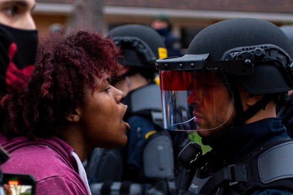 A woman yells while facing an expressionless cop in riot gear