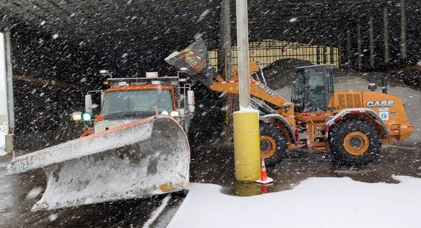 A loader fills a plow with salt.