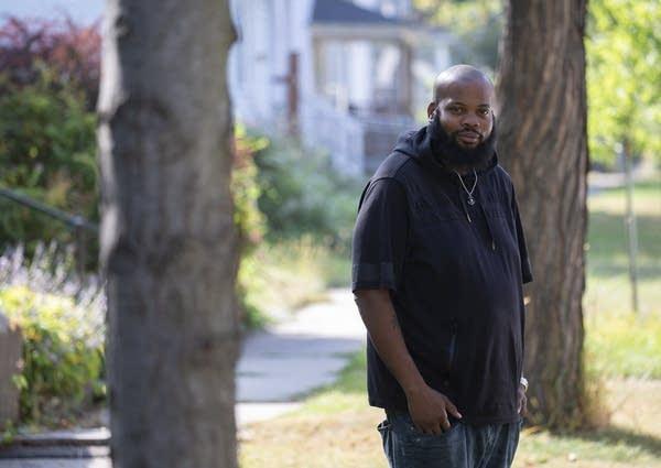 A man standing outside in a neighborhood.