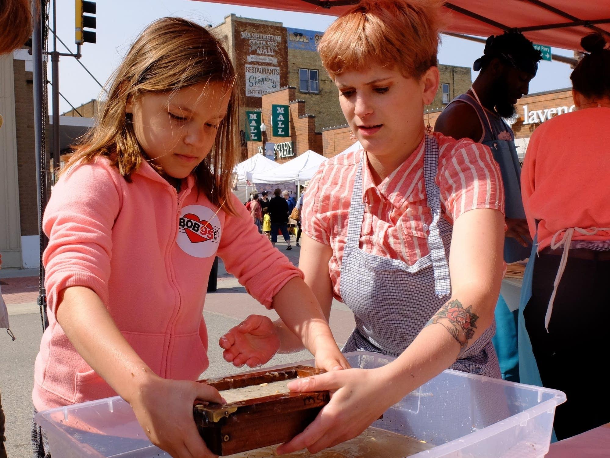Amanda Frost (right) helps Hattie Devries (left) make a sheet of paper.