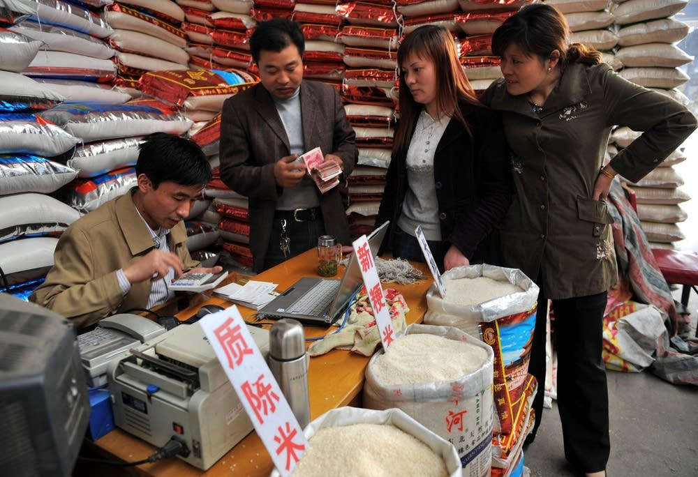 A rice vendor in China calculates prices of rice