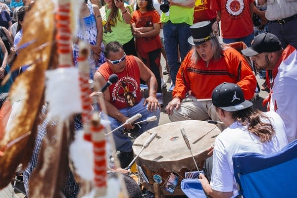 Dakota men play a song on drums.