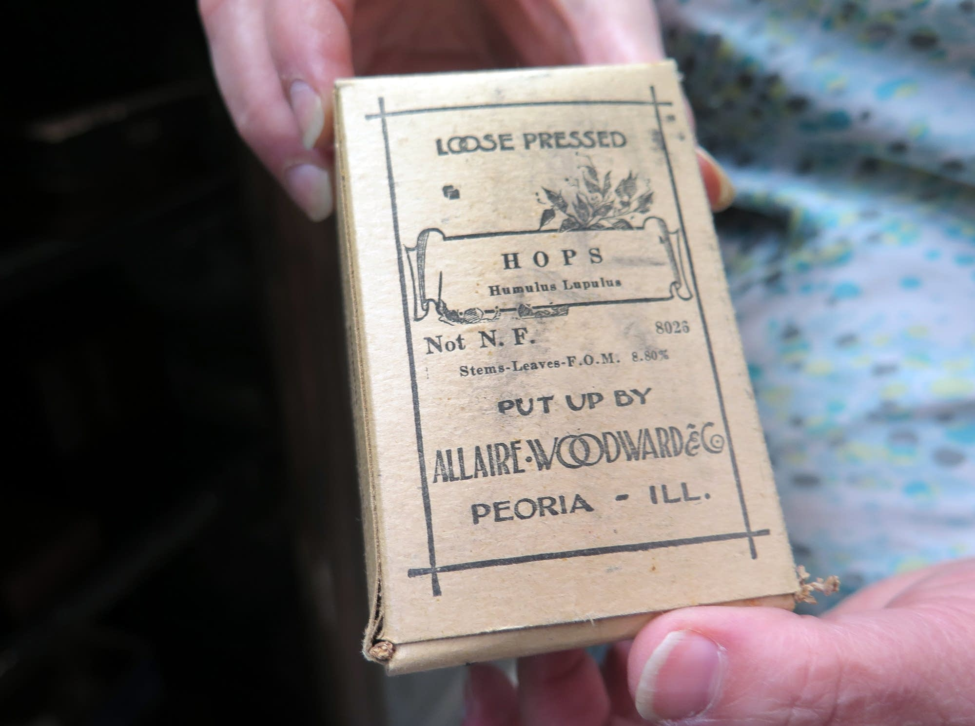 The curator of the Wangensteen Library holds up a box on medicinal hops.