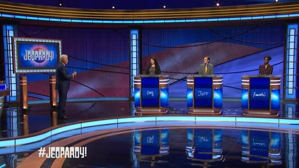 Wide shot of Jeopardy! set showing Alex Trebek and 3 contestants spaced out