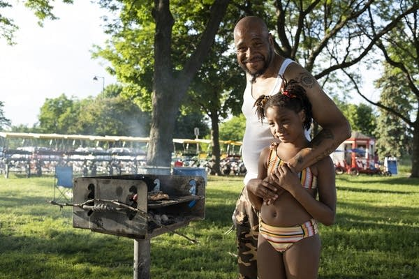 A dad and his father stand next to a grill.