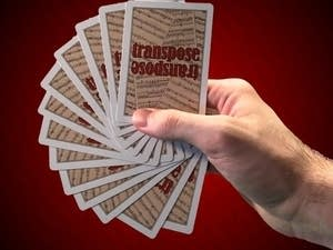 Hand holding fanned out cards.