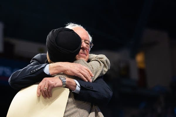 A man hugs a woman on a stage.