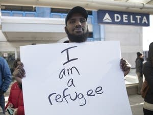 Aidarus Aden, a refugee from Somalia, holds a sign.