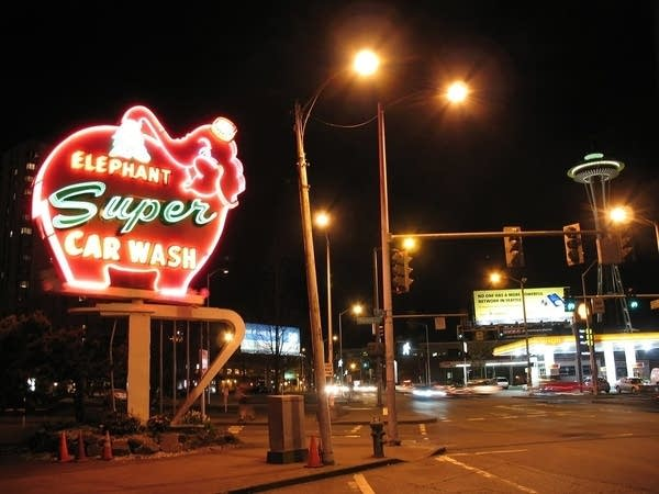 Night photo of neon car wash sign shaped like pink elephant in Seattle