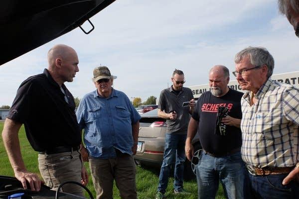 Men talk near a car