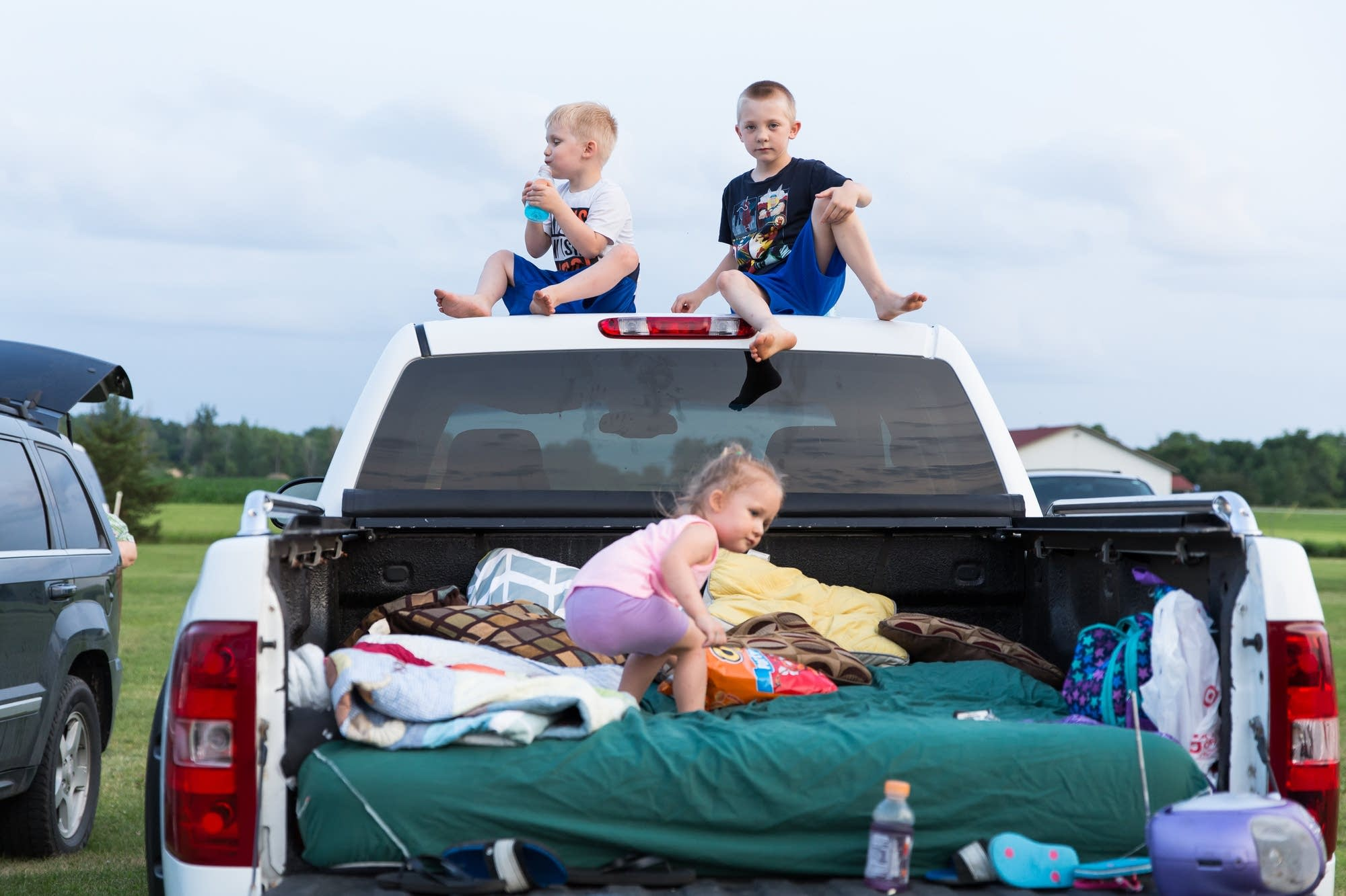 Siblings play on the back of their family's pick-up truck.