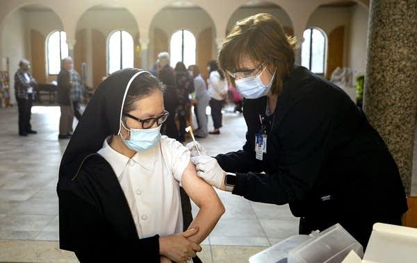 A woman receives a vaccine.