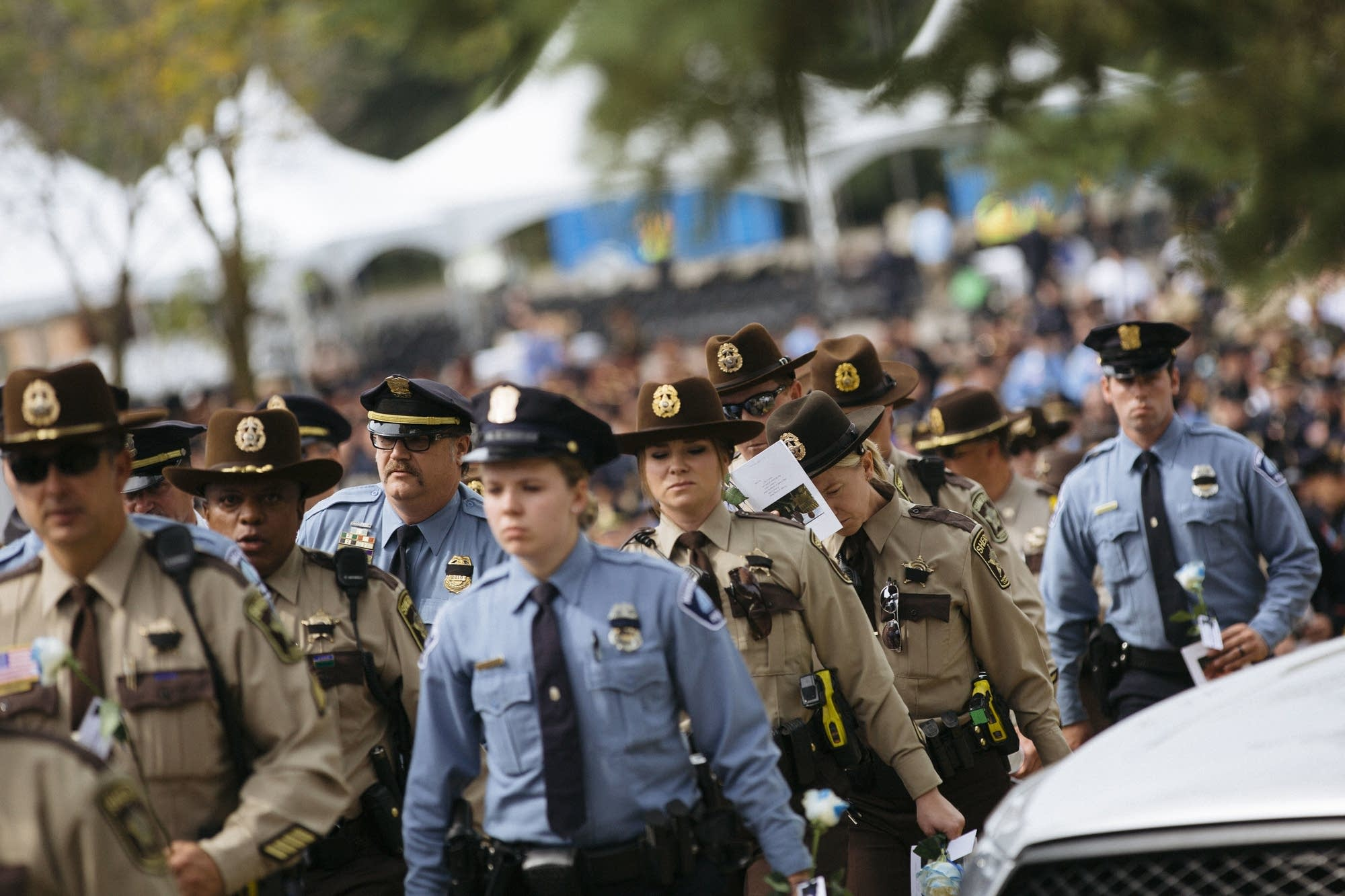 Police officers and state troopers leave the funeral service.
