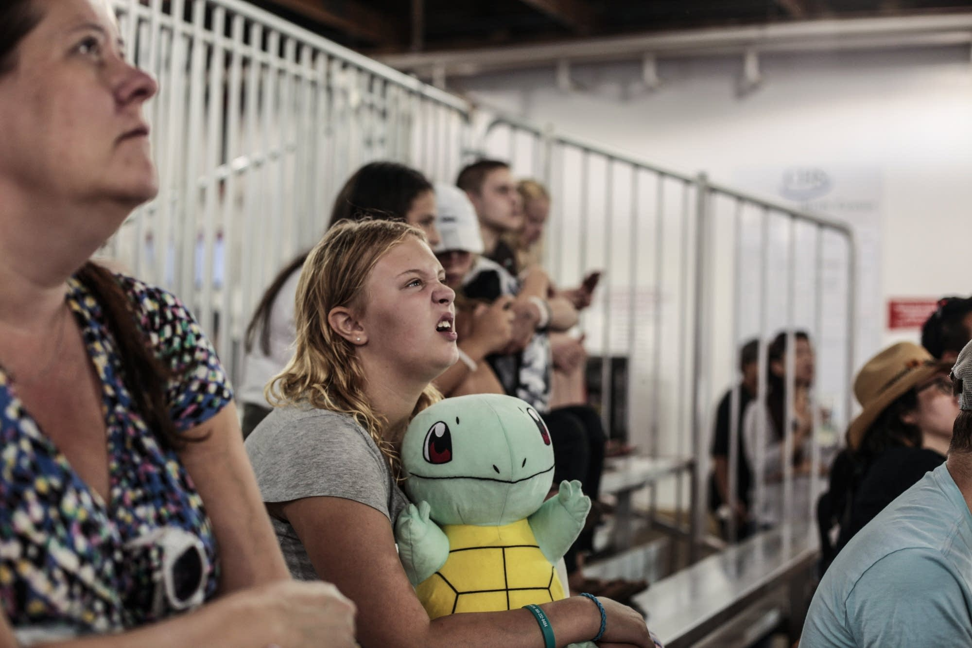 A girl holding a Squirtle pokemon doll watches the miracle of birth videos.