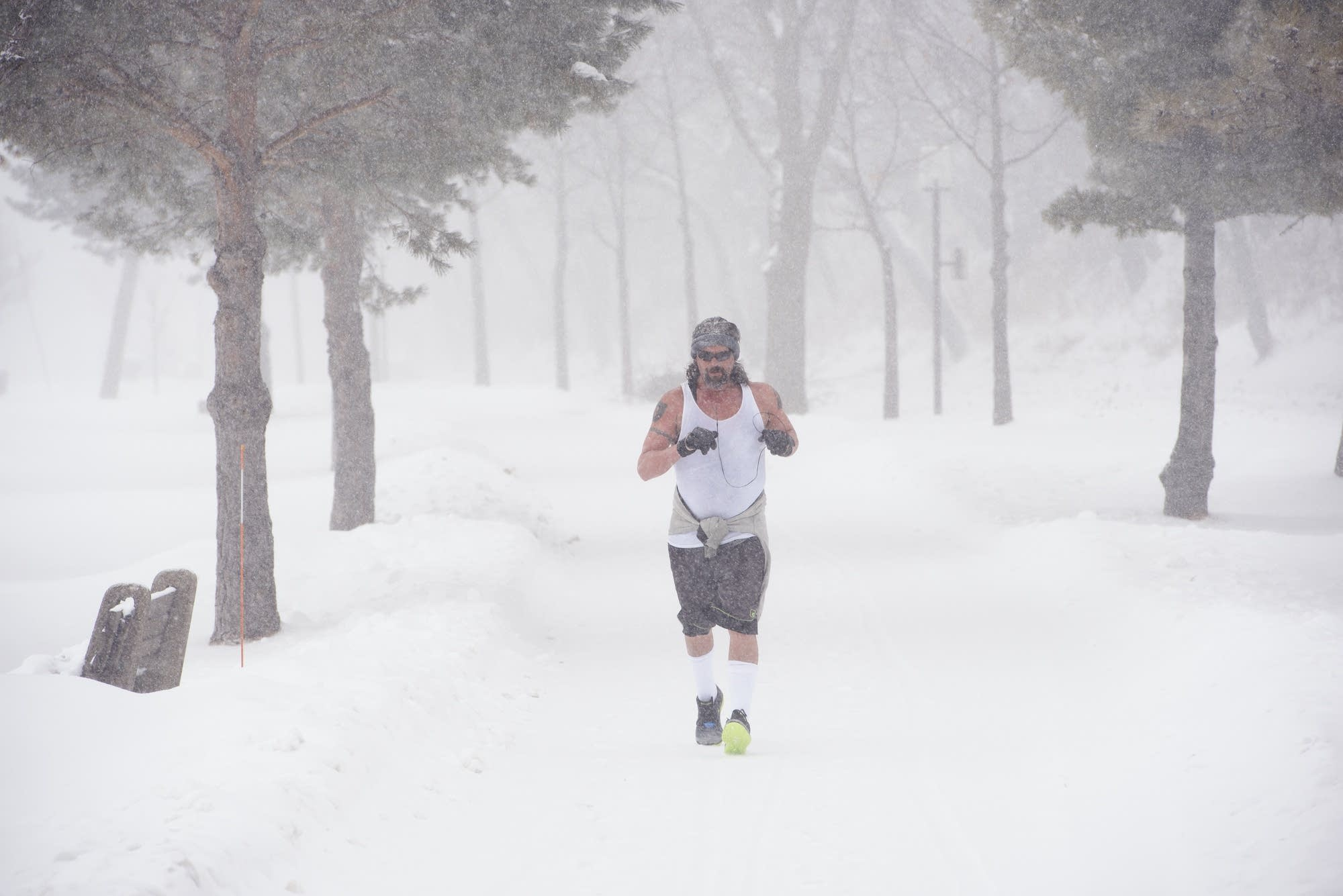 Unperturbed by the day's snowy weather, a man runs along Lake Calhoun.