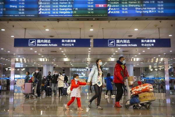 Travelers in face masks walk past a display board.