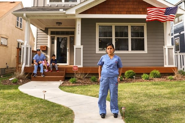 A woman wearing hospital scrubs stand outside her home.
