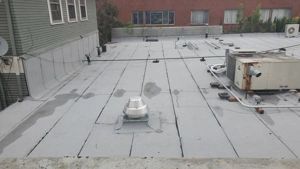 Top of a flat, gray roof w/ air conditioning unit and puddles of water