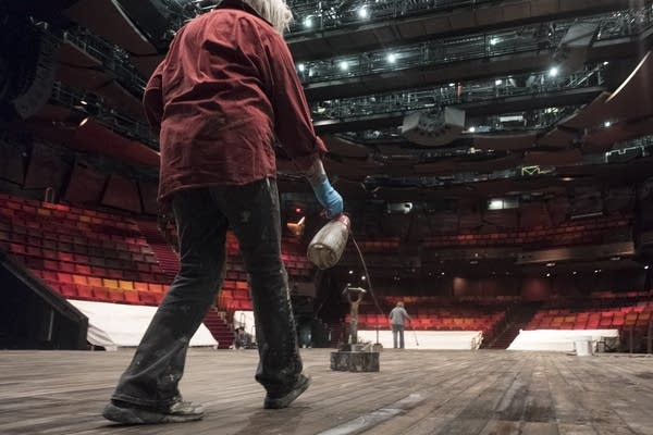 Rebecca Pavlenko paints the wooden floor of a stage.